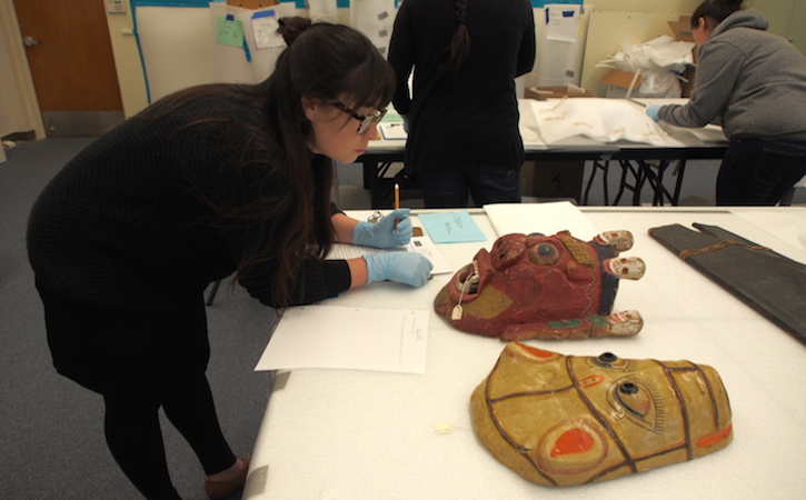 Museum Studies student studying and object from the collection.