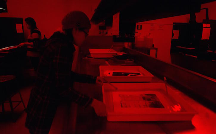 Student in photography dark room.